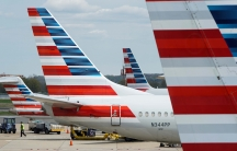 A member of a ground crew walks past American Airlines planes parked at the gate during the coronavirus disease (COVID-19) outbreak at Ronald Reagan National Airport in Washington, DC, April 5, 2020.