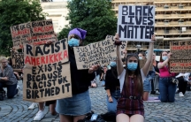 People wearing protective face masks hold up signs during a protest