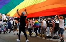 A group walks under a large rainbow flag.