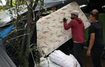 A man wearing a face mask carries a mattress at a makeshift camp