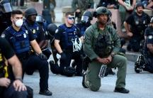 Men in police uniform kneel on an urban street.