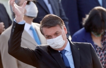 Brazil's President Jair Bolsonaro wearing a protective face mask gestures during a national flag hoisting ceremony in front of Alvorada Palace, amid the coronavirus disease (COVID-19) outbreak in Brasilia,Brazil, June 9, 2020.