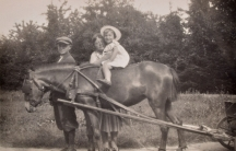 A black and white photograph of girl on a pony with two people around her
