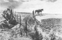 A black and white photograph of a man tilling soil