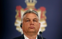 A close-up photo of Hungarian Prime Minister Viktor Orban wearing headphones