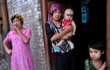 An ethnicUighurwoman hugs her son as she stands outside her house with her daughter and neighbors