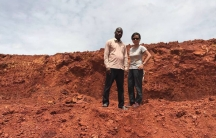 Two people are shown in the distance standing on a brown dirt and rock ledge.