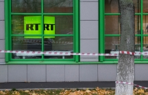 Russian state-owned television station RT logo is seen through a window with caution tape in front of a building