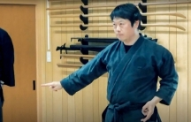 A man wears black and practices a ninja move.