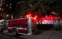 The rear of a red fire truck is shown with lights on outside of a building with trees in the background.