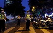 Several security personnel are shown standing in the street and wearing reflective vests next to police motorcycles.