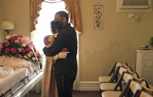 Siblings Erika and Dwayne Bermudez comfort one another during a short viewing of their mother, Eudiana Smith, at The Family Funeral Home, May 2, 2020, in Newark, New Jersey.