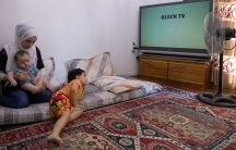 Syrian refugee mother holds 6-month-old son as toddler looks at the TV