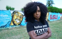 A black woman wearing a black shirt with white lettering poses near a mural