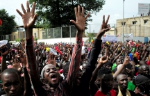 A huge crowd of protesters in Mali with one person raises his arms high in the air