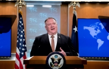 A man wearing a suit stands at a State Department podium between two flags