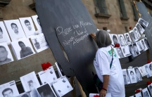A woman wearing a white shirt signs a black silhouette during a demonstration for mothers of enforced disappearances