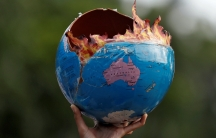 A person holds a replica of a burning globe in the air with fake flames coming out of it.