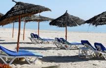 Empty sun beds on an empty beach with blue sky