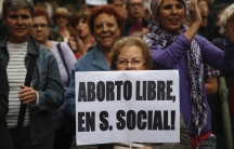 """A woman holds a banner that reads """"Free abortion covered by social security"""" during a pro-choice march to celebrate the government ending its plan to reform Spain's abortion law in Madrid September 28, 2014. Spanish Prime Minister Mariano Rajoy on Tuesday"""