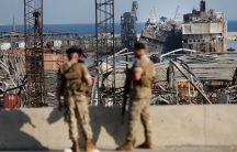Two soldiers are shown in the near ground in soft focus with widespread rubble from Beirut's destroyed port in the destance.