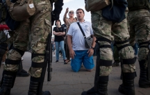 A man is shown kneeling on the ground in front of several security officers dressed in camoflage and carrying weapons.