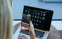 A woman holds a mobile phone up to her laptop screen in a video call showing various apps.
