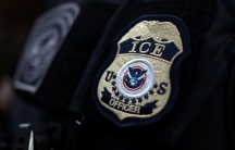 The sewn badge of an ICE officer is shown on the shoulder of an offfical.