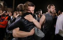 A man and a woman are shown hugging with several people nearby taking photographs.