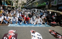 A large group of men are shown sitting in a street with cardboard cutouts of President Donald Trump and Abu Dhabi Crown Prince Mohammed bin Zayed al-Nahyan and Israeli Prime Minister Benjamin Netanyahu lay on the ground in front of them with shoes placed.