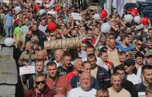 A large crowd of people are shown en mass holding signs on a bright sunny day.