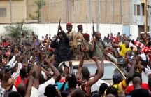 A large crowd of people are shown with their hands in the air cheering a group of armed soldiers in a car.