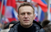 A close-up photograph of Alexei Navalny wearing a dark puffy jacket.