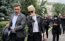 Alexei Navalny's wife Yulia, center, is shown walking and being followed by members of the media.