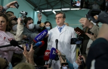Chief physician Alexander Murakhovsky is shown wearing a white lab coat and tie while surrounded by members of the media.