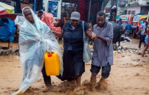 Two men are shown helping a woman as they wade through a flooded street.