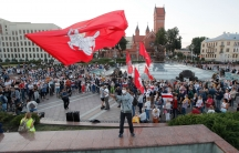 A large crowd of people are shown in a public square in Minsk with a man in the center of the photograph wave a large red Belarusian flag.