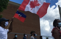 With Canadian and Haitian flags hoisted, marchers take part in demonstration in support of asylum-seekers working in Quebec's long-term care homes in Montreal, Canada, in June.