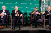 Four white men in suits sit on a panel with a green background