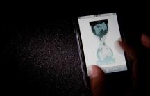 A hand holds a smartphone with Wikileaks webpage logo
