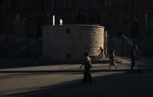 A few people walk or bike in shadows near a large building.