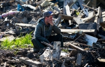 A man squats in rubble holding his head in a perplexed way