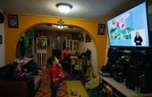 A child looks at a TV screen in a living room with orange painted walls.