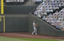 A baseball player watches a foul ball go into stands filled with photos of fans.