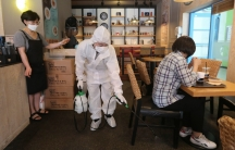 A worker dressed in white protective gear disinfects as a precaution against the coronavirus at a café in Goyang, South Korea,Aug. 25, 2020.