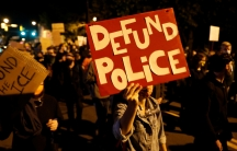 """Demonstrators hold a sign reading """"Defund the police"""" during a protest over the death of a Black man, Daniel Prude, after police put a spit hood over his head during an arrest on March 23, in Rochester, New York, September 6, 2020."""
