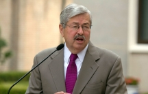 US Ambassador to China Terry Branstad is shown wearing a tan suit and a purple tie while speaking into a small microphone.