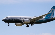 A Boeing 737 Max jet is shown in the air with its wheels down prepared for a landing.