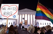 A crowd of people are shown in the dark of night outside of the brightly lit facade of the US Supreme Court and holding signs and flags.