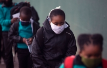 A line of young school children are shown wearing face masks and wearing backpacks and jackets.